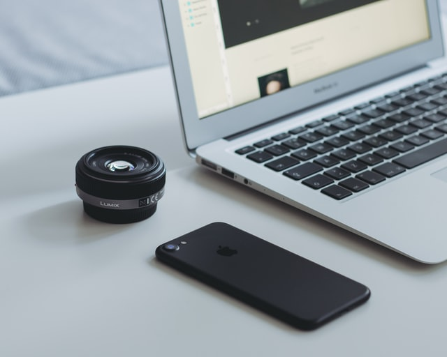 A phone , camera lens and laptop